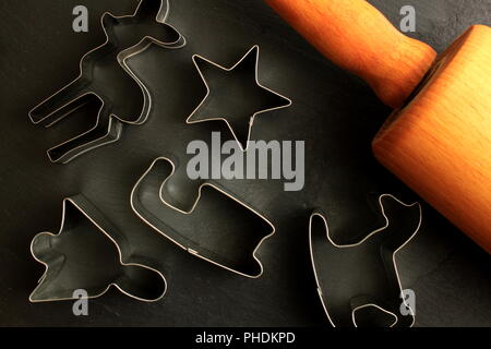 Christmas cookie cutters with wooden rolling pin on black background - Stock Photo