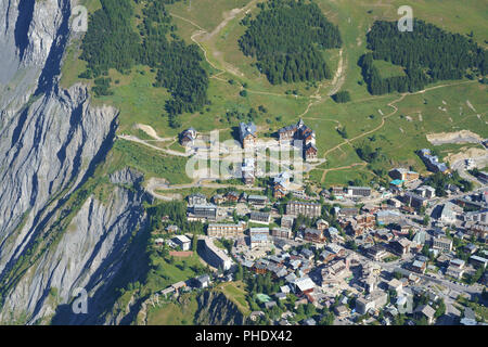 TOO CLOSE FOR COMFORT HEADWARD EROSON AT THE CITY'S LIMIT (aerial view). Ski resort of Les 2 Alpes in summer, France. - Stock Photo