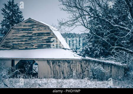 Fresh snow sits on the ground around an old barn - Stock Photo