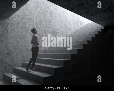 woman climbs the stairs from darkness to light - Stock Photo