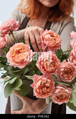 girl in an apron holds a rose in her hands - Stock Photo