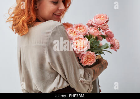 A happy girl holds a vase with a pink roses - Stock Photo