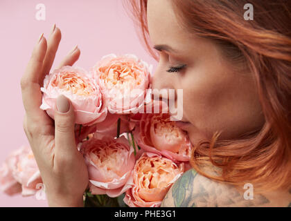 Cute woman is sniffing a bouquet of pink Buttercup Asian - Stock Photo