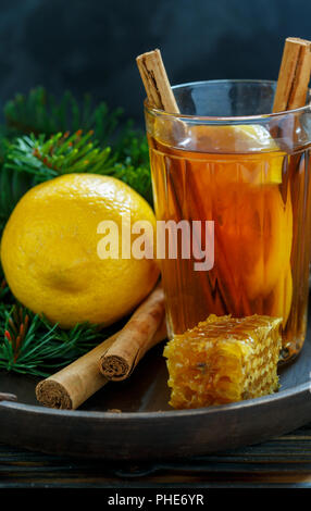 Hot tea with spices and lemon on a wooden tray. - Stock Photo