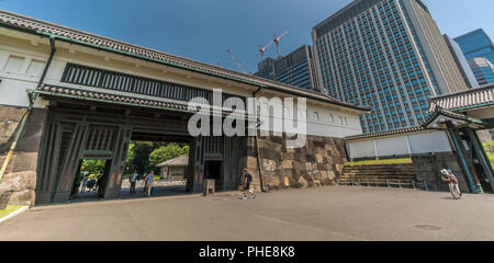 Tokyo, Chiyoda Ward - August 5, 2018 : Tourists passing through Ote-mon Gate entrance of Imperial Palace East Gardens Ninomaru on a clear day. Otemon  - Stock Photo