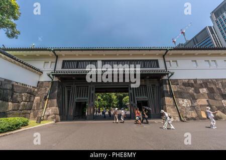 Tokyo, Chiyoda Ward - August 5, 2018 : Tourists passing through the Ote-mon Gate entrance of Imperial Palace East Gardens Ninomaru on a blue sky clear - Stock Photo