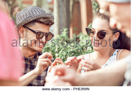 Teenage couple picking daisies in park - Stock Photo