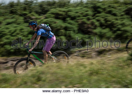Woman mountain biking through field in Porlock Weir, England - Stock Photo