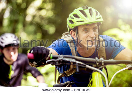 Man pushing mountain bike in forest - Stock Photo