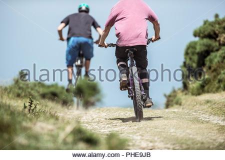 Men mountain biking in Porlock Weir, England - Stock Photo