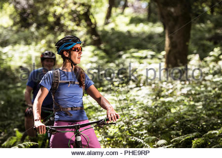 Couple mountain biking in forest - Stock Photo