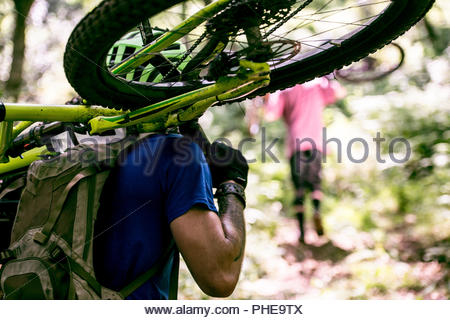 Man carrying his mountain bike in forest - Stock Photo