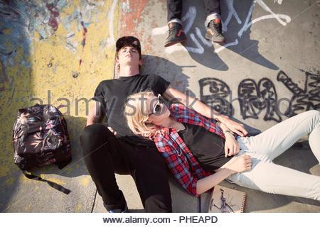 Teenage couple lying down at skatepark - Stock Photo