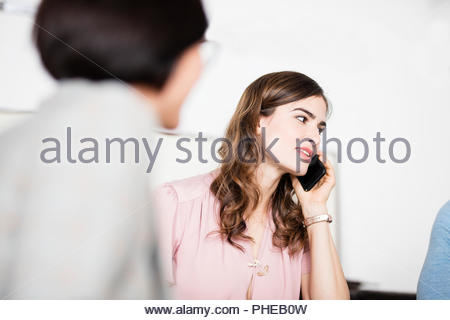 Young businesswoman talking on smartphone during meeting - Stock Photo
