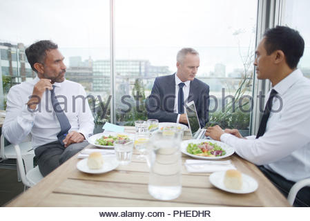 Businesswomen looking at smartphone in restaurant - Stock Photo