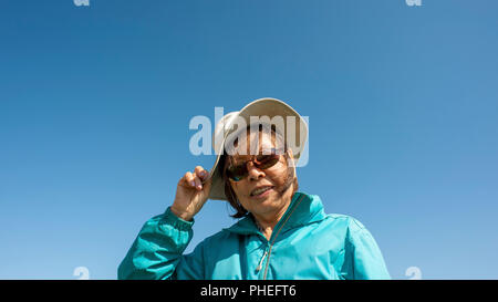 Mature Asian lady wearing blue anorak, floppy canvas hat and sun glasses, holds onto  her hat  in strong wind. - Stock Photo
