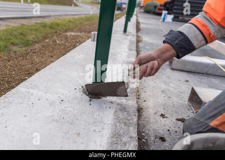Bricklayer concreted with a plastering trowel - closeup masonry work - Stock Photo