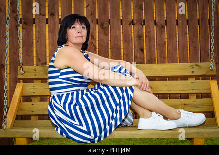 brown-haired middle-aged woman in the village toning - Stock Photo