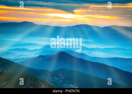 Blue mountains and hills under sunset - Stock Photo
