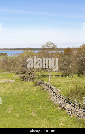 Rural countryside view with a stone wall in early spring - Stock Photo