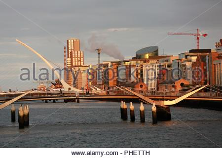 The beauty of a Dublin sunset as the light goes down on the River Liffey and the Samuel Beckett bridge - Stock Photo