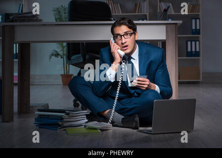 Businessman working overtime long hours late in office - Stock Photo