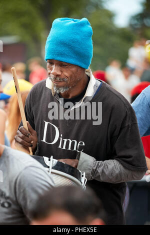 African American male playing rhythm on a drum at Tam Tams festival in Mount Royal Park, Montreal, Quebec, Canada. - Stock Photo