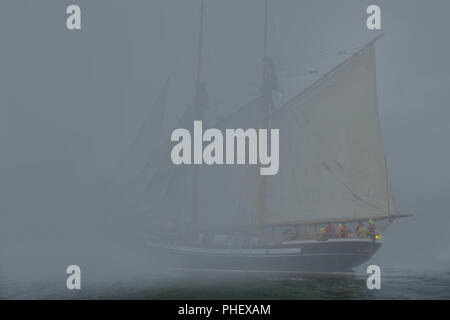 Two masted Schooner with sails on port-side tack sails into dense fog - Stock Photo