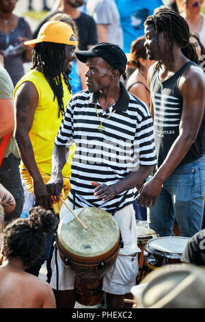 African American male percussionist playing his djembe drum bongo at Tam Tams festival in Mount Royal Park, Montreal, Quebec, Canada. - Stock Photo