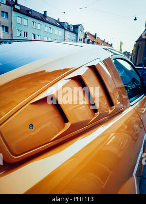 close up view on a orange and black mustang in the city - Stock Photo