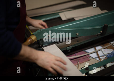 Man cutting paper and card on a large guillotine on a work table in a book binders workshop in a close up view - Stock Photo