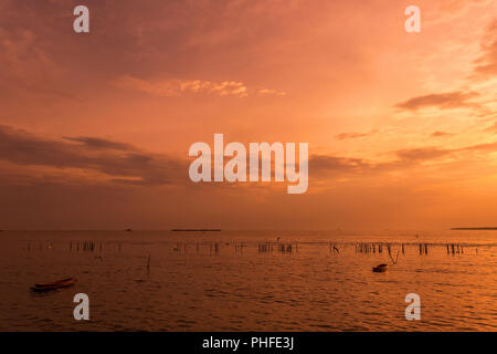 lonely wooden fisherman boat with the seagulls when sunset / sunrise on the sea a freedom and peaceful - Stock Photo