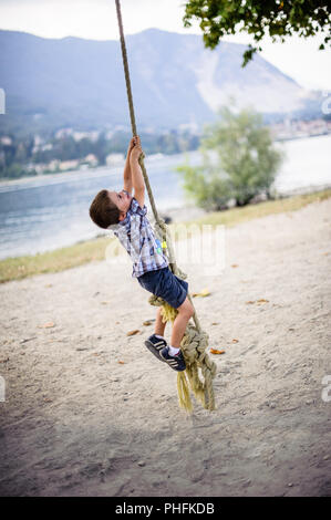 child boy climbs on a big rope in the outdoor - Stock Photo