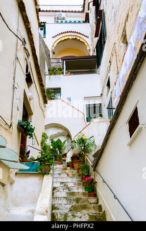 Narrow street and courtyard in Amalfi town, southern Italy - Stairs lead to the doors of residential buildings - Stock Photo