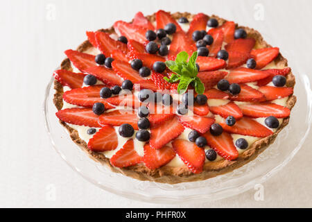 Homemade cheesecake decorated with organic strawberries, blueberries and fresh mint and cream. Nice pie for a holiday celebration or any birthday part - Stock Photo