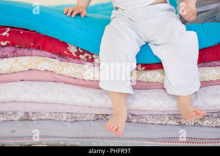 Small baby boy in white trousers sitting on a pile of colorful blankets and mattresses. Happy childhood. Leisure. Indoors. barefoot boy in the bedroom - Stock Photo