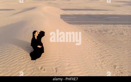 woman in a traditional emirati dress called abaya in a desert near Dubai - Stock Photo
