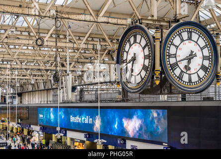 Large old four faced clock hanging at London Waterloo station, London, England, UK - Stock Photo
