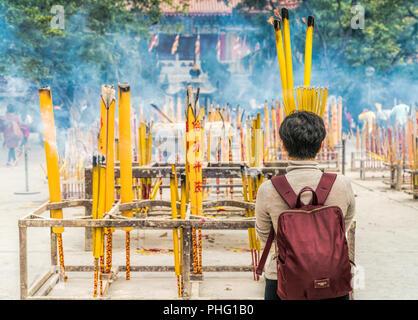 19 February 2018 - Lantau Island, Hong Kong. Woman praying with yellow burning incense sticks at Po Lin Monastery, located in Lantau Island, Honkg Kon - Stock Photo