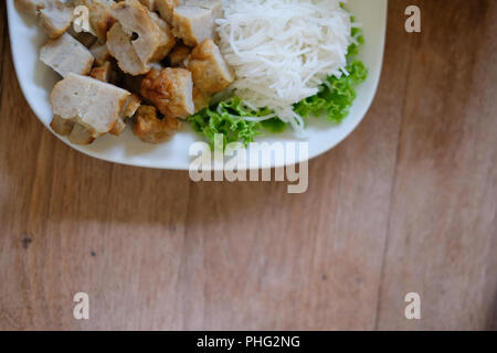 minced pork sausage, fermented rice noodle & vegetable served with chili sauce. vietnamese summer roll food called Nem Nuong Xa - Stock Photo