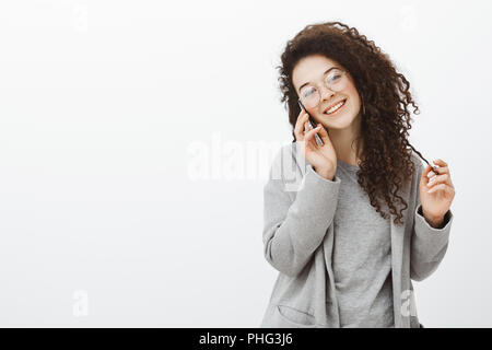 Waist-up shot of outgoing friendly stylish girl with curly hair in stylish eyewear and grey coat, talking on smartphone, tilting head and smiling broadly, sharing stories with friend abroad - Stock Photo