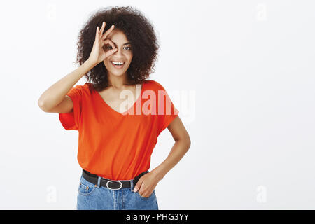 Girl is sure in her abilities. Good-looking positive woman with afro haircut, holding hand in pocket and showing okay or great sign over eye, smiling broadly while liking or confirming something - Stock Photo