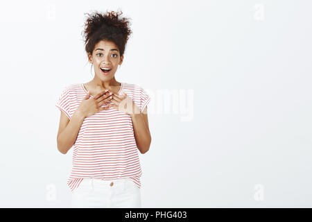 Girl surprised with unexpected gift. Portrait of pleased happy charming woman with dark skin and combed curly hair, holding hands on chest and dropping jaw, being amazed and joyful receive present - Stock Photo