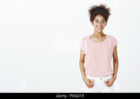 Indoor shot of friendly-looking carefree female student in glasses and striped t-shirt, holding hands on jeans and smiling broadly at camera, talking to boyfriend and feeling happy over gray wall - Stock Photo