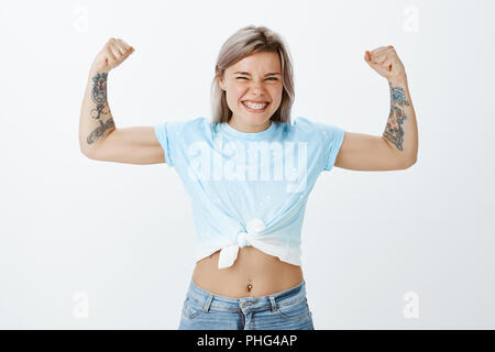 Show me real power of muscles. Portrait of good-looking playful and emotive girl with tattooed arms, raising hands and showing biceps while smiling broadly, working out for summer over grey wall - Stock Photo
