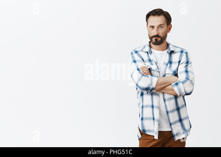 Man nervously listening to wife wanting confess in something. Intense worried serious-looking mature masculine male with beard, holding hands crossed, pursing lips and staring seriously at camera - Stock Photo
