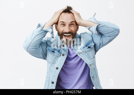 Cannot believe it happen to me. Joyful happy and excited caucasian male model, touching hair and smiling broadly while gazing with satisfaction and amusement at camera, winning lots of money - Stock Photo