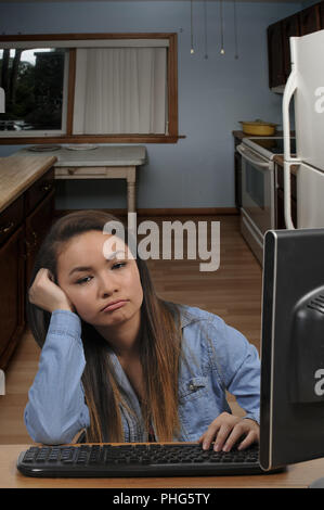 Teenage girl doing homework on a computer - Stock Photo