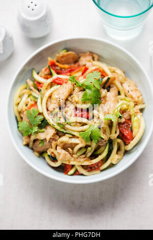 Vegetarian stir fry with chilli & coriander soya chunks with spiralled courgette spaghetti and semi dried tomatoes - Stock Photo