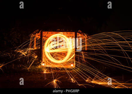 Long exposure image of steel wool photography, light painting in wooden house. - Stock Photo
